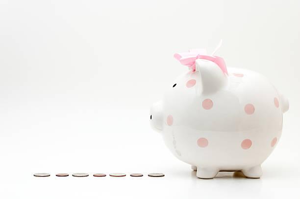 rosa sparschwein auf eine reihe von münzen - rentenpunkte stock-fotos und bilder