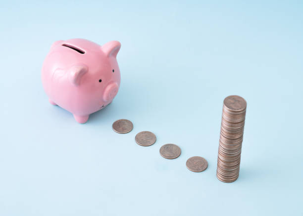 Pink piggy bank following a line of coins to big money stock photo