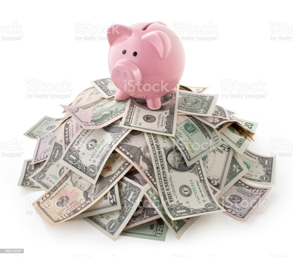 Pink piggy bank on pile of U.S. bills stock photo