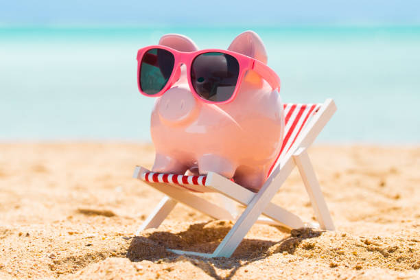 Pink Piggy Bank On The Deck Chair At Beach Pink Piggy Bank With Sunglasses On The Small Deck Chair At Beach 40 kilometre stock pictures, royalty-free photos & images
