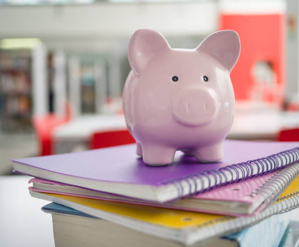 Pink piggy bank on top notebooks - Student loans Pink piggy bank on top notebooks - Student loans fee stock pictures, royalty-free photos & images
