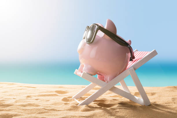 Pink Piggy Bank Relaxing On Deck Chair Close-up Of A Pink Piggy Bank Wearing Sunglasses Relaxing On Deck Chair 40 kilometre stock pictures, royalty-free photos & images