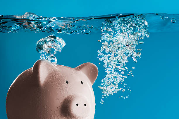 A pink piggy bank sinking in water A pink ceramic piggy bank is drowning underwater. There are air bubbles rising from the top of the pig and from the front of the pig where its mouth is. The surface of the water is uneven as where the pig has been fighting to get to the surface. sunken stock pictures, royalty-free photos & images