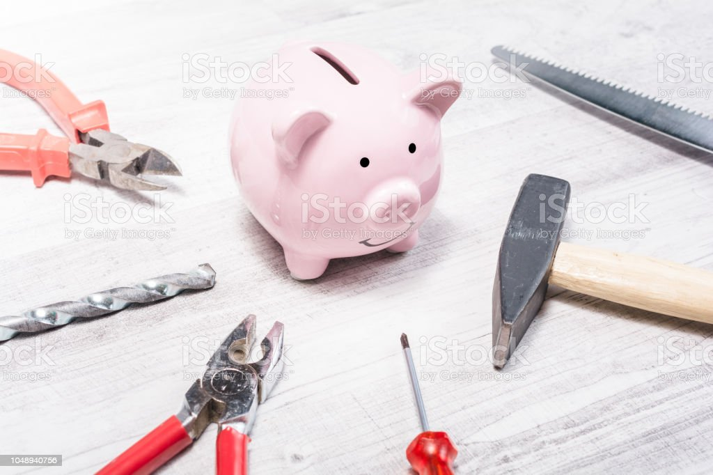 Pink Piggy Bank Surrounded By Tools Like Hammer Pliers Or Saw Open