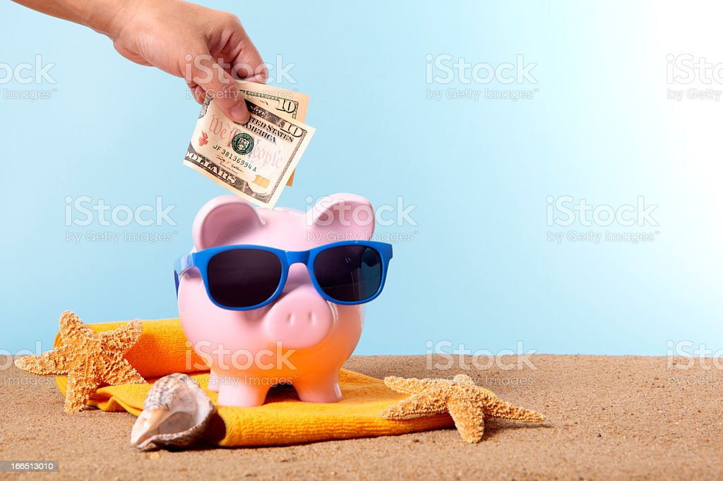 Pink piggy bank with beach items and money being put in stock photo