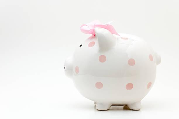 rosa sparschwein mit rosa polka dots und schleife - rentenpunkte stock-fotos und bilder