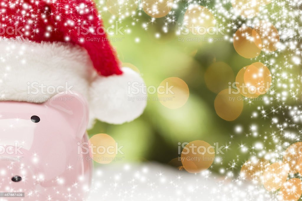 Pink Piggy Bank with Santa Hat on Snowflakes stock photo