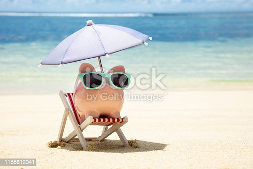 Pink Piggybank With Sunglasses And Umbrella On Deck Chair On Sand At Beach