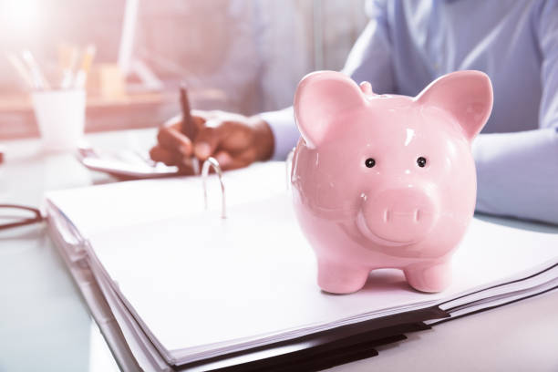 Pink Piggybank Over The Open Folder At Workplace Businessman Calculating Invoice In Front Of Pink Piggybank On Folder 401k stock pictures, royalty-free photos & images