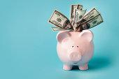 istock Pink piggybank stuffed with dollar bills 184860418