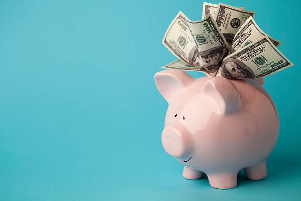 Pink piggybank stuffed with dollar bills stock photo
