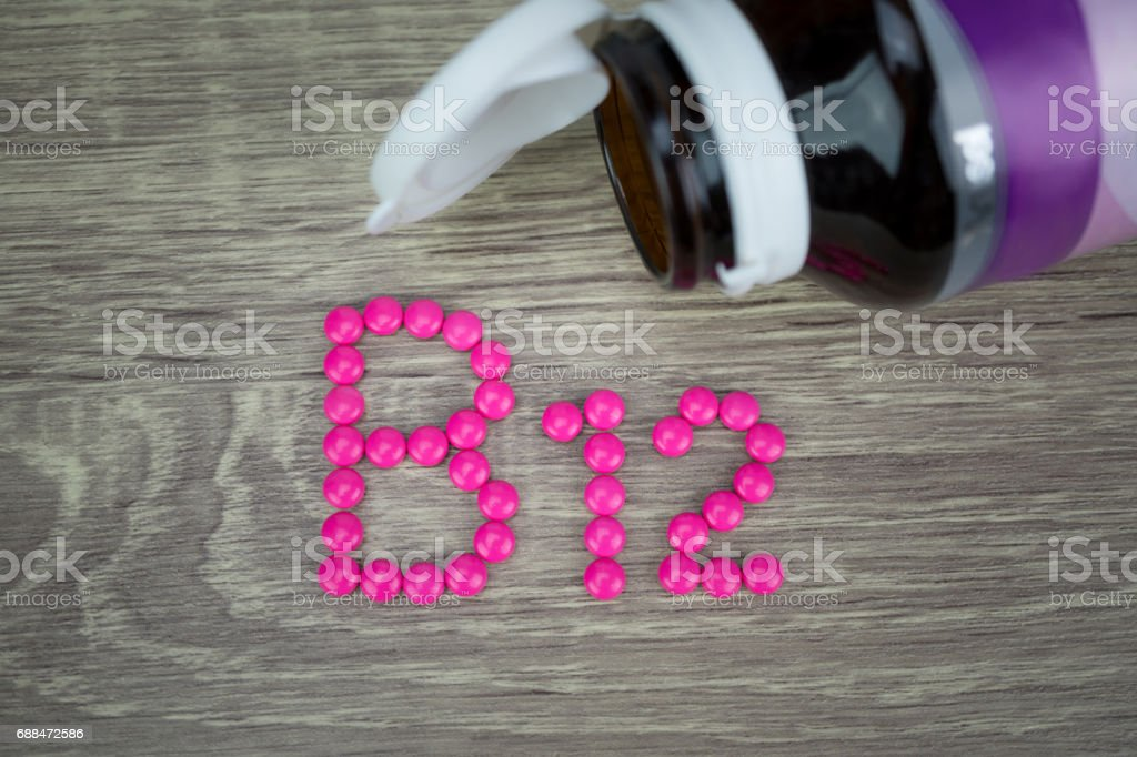 Pink pills forming shape to B12 alphabet on wood background stock photo
