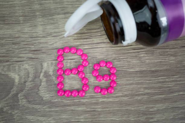 Pink pills forming shape to B9 alphabet on wood background stock photo