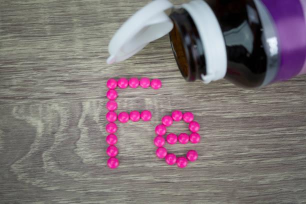 在木質背景下形成形狀為 fe 字母的粉紅色藥丸 - 鐵 個照片及圖片檔