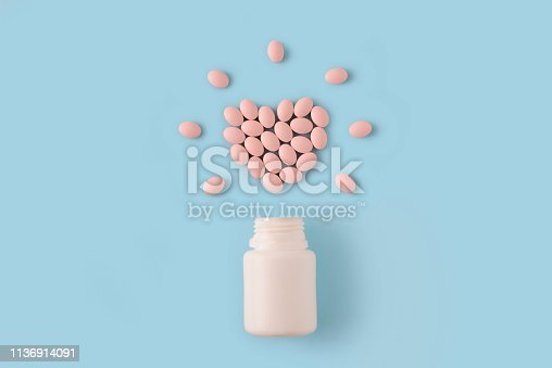 istock Pink pills in shape of heart and bottle on blue background. Medical pharmacy concept. 1136914091