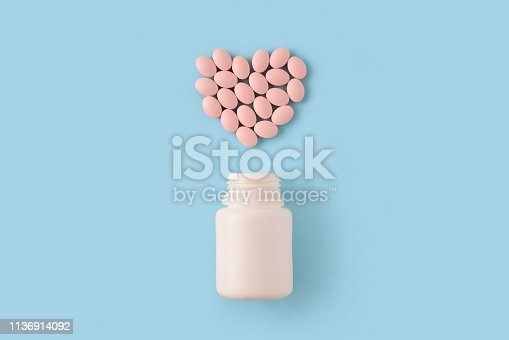 istock Pink pills in shape of heart and bottle on blue background. Medical pharmacy concept. 1136914092