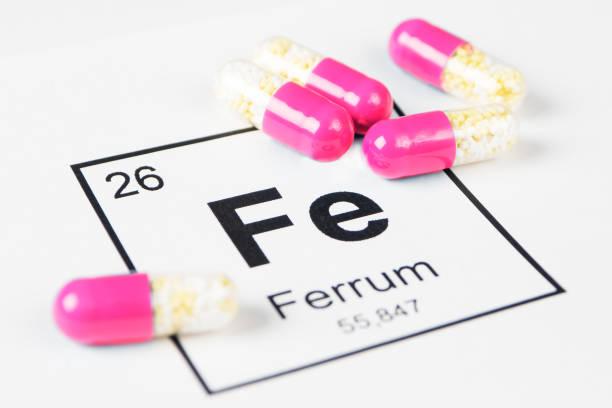 粉紅色藥丸與礦物 fe (鐵) 在白色背景與題字從化工桌 - 鐵 個照片及圖片檔