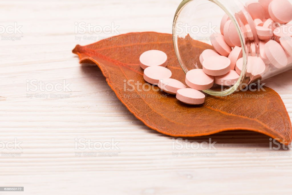 Pink pills with orange leaf stock photo