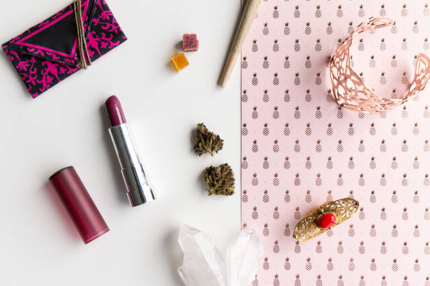 Pink Pineapples and Lipstick Woman's Accessories for Cannabis Tourism or Festival with a Joint, Nugs, and Edibles, Lipstick, Weed Pouch, Rose Gold Jewelry, in Disarray - Top Down stock photo