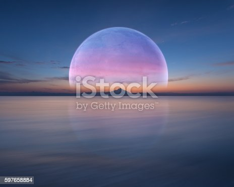 istock Pink planet like moon above the ocean and mountain 597658884