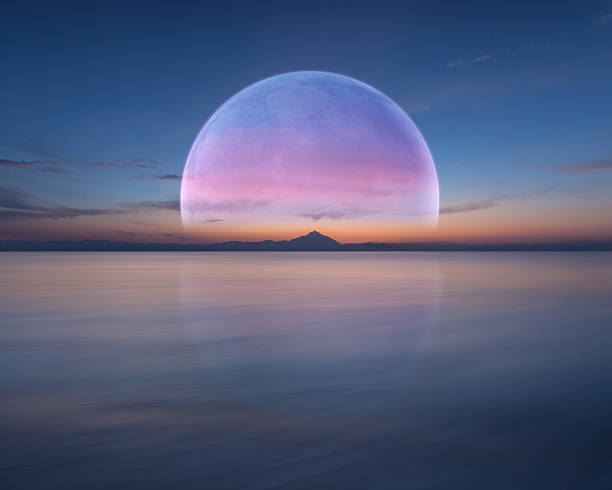 Pink planet like moon above the ocean and mountain - foto de stock