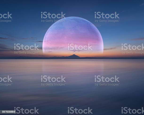 Photo of Pink planet like moon above the ocean and mountain