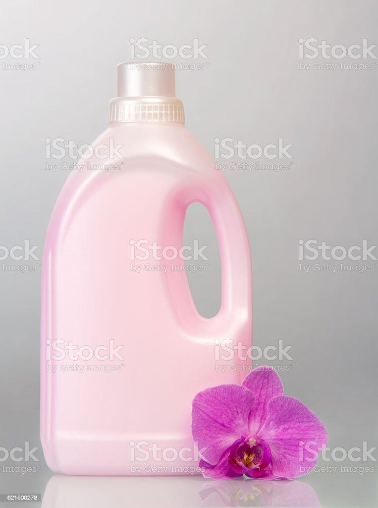 Pink plastic bottle with liquid detergent, orchid flower on gray. photo libre de droits