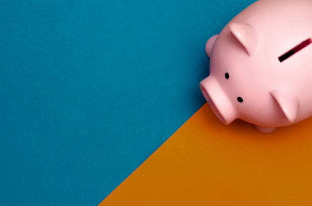 Pink plastic piggy bank on pink background with copyspace stock photo