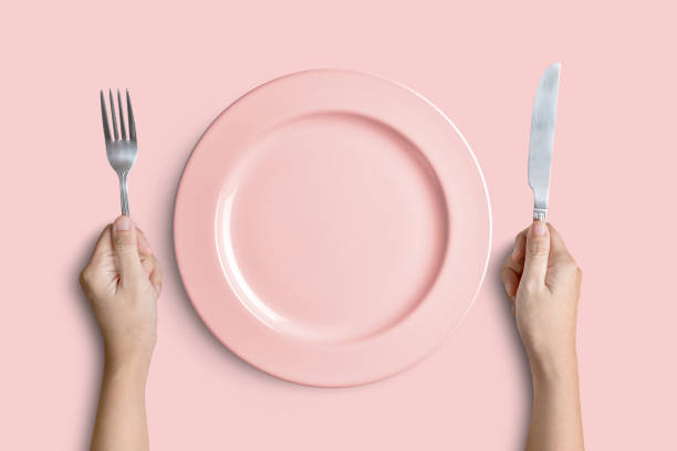 Pink plate with silver fork and knife on pink background Dinner place setting. A pink plate with silver fork and knife isolated on pink background with clipping path hungry stock pictures, royalty-free photos & images