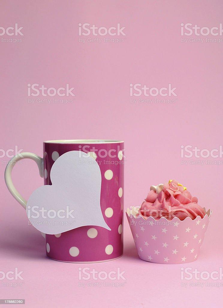 Pink polka dot coffee mug with cupcake. Vertical. royalty-free stock photo