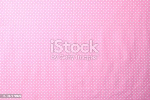 Overhead shot of pink polka dot fabric texture background.