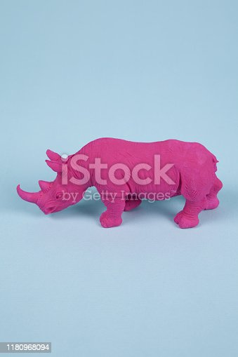 a pink fuschia rhinoceros, set on a blue background. Pop atmosphere. minimal color still life photography pop atmosphere. Minimal color still life photograph