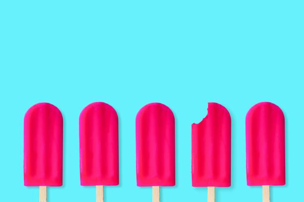 Pink popsciles on a pastel blue background. One with bite removed. stock photo