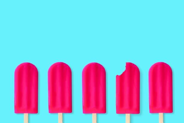 popsciles rose sur fond bleu pastel. une avec la morsure enlevée. - couleur vive photos et images de collection