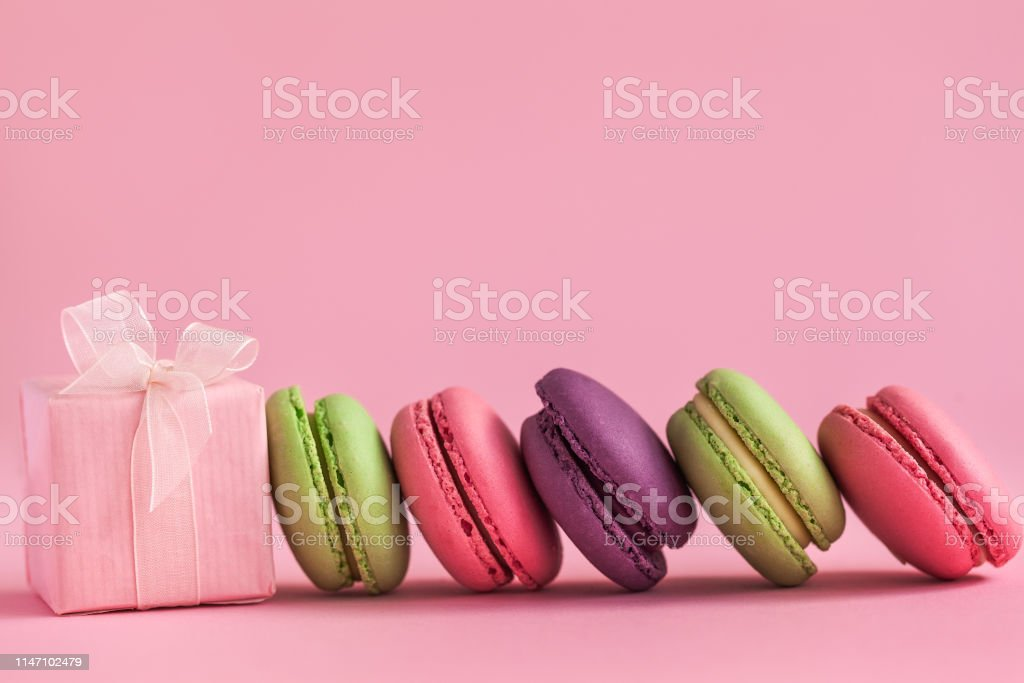 Pink present and Row of french colorful macaroons, lying on pink...