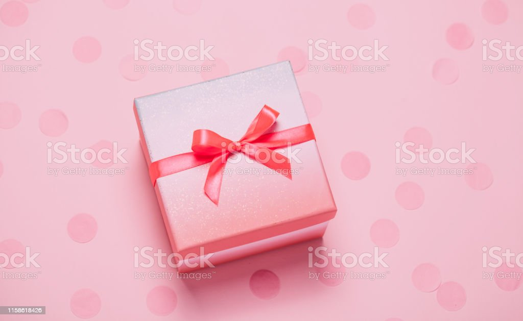 Pink present box on pink konfetti background. Top view, flat lay....