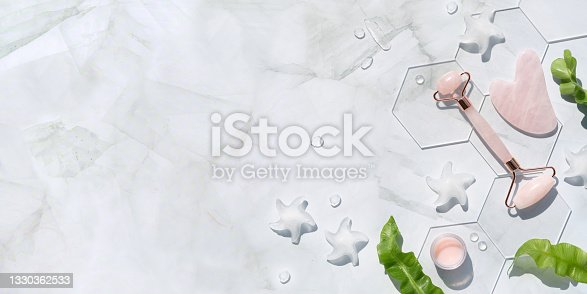istock Pink Quarts stone face roller, cream, hexagons. Gua sha stone for beauty facial massage therapy. Natural cosmetics laboratory. Off white flat lay with palm leaf shadow, text space 1330362533