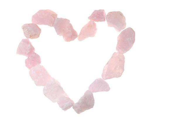 pink quartz. heart made of pink quartz stones on white background - rose quartz stock photos and pictures