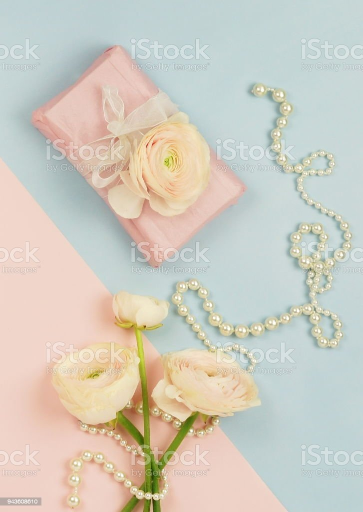 Pink Ranunculus Flowers Gift Box And Pearl Necklace On Blue Pale Background Top