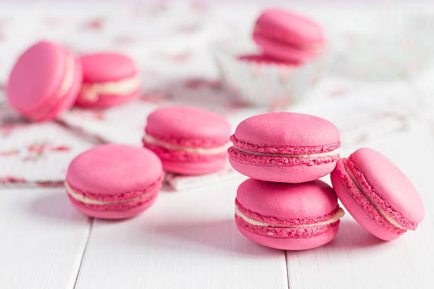 Pink raspberry macaroons on white wooden background stock photo
