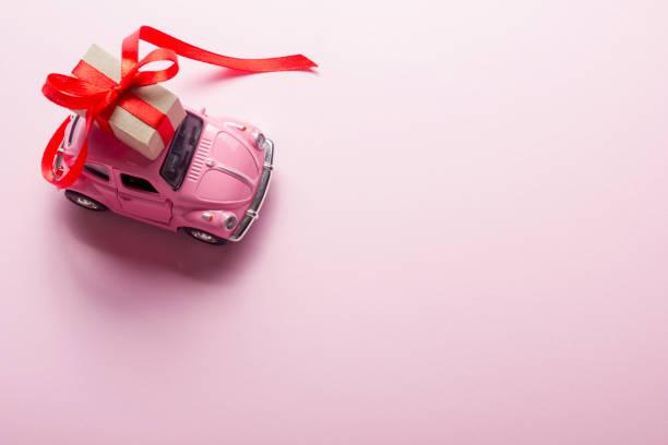 rosa retro spielzeugauto geschenk-box auf pastell hintergrund zu liefern. ansicht von oben - originelle geburtstagsgeschenke stock-fotos und bilder