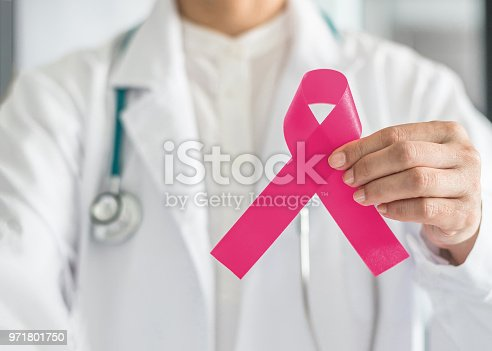 istock Pink ribbon for breast cancer awareness in doctor's hand, symbolic bow color for raising awareness campaign on women (female)  patient living with breast tumor illness 971801750