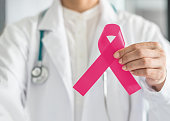 Pink ribbon for breast cancer awareness in doctor's hand, symbolic bow color for raising awareness campaign on women (female)  patient living with breast tumor illness