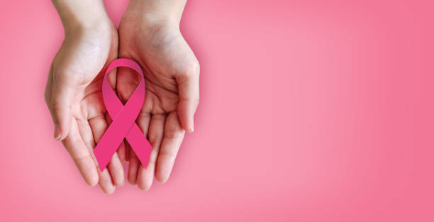 Pink ribbon on hands for breast cancer awareness stock photo