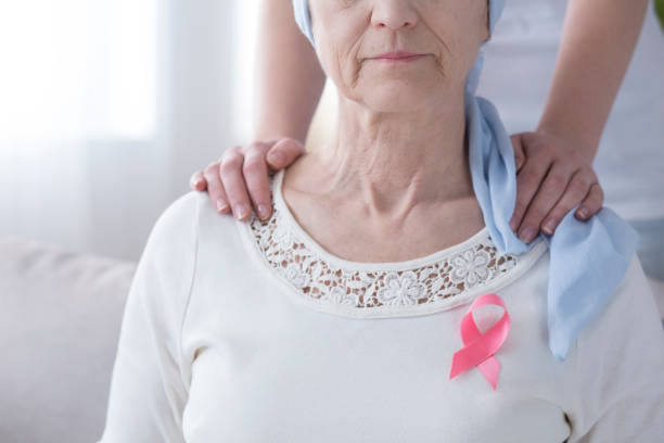 Pink ribbon on sick woman Breast cancer awareness concept - pink ribbon on a sick, older woman and supportive hands on her shoulder chemotherapy cancer stock pictures, royalty-free photos & images