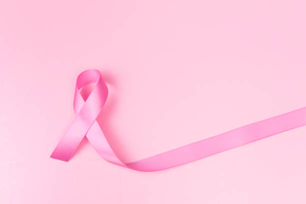 pink ribbon symbol for breast cancer awareness concept over pink background with copy space for text, logo or wordings insertion - breast cancer awareness ribbon stock pictures, royalty-free photos & images