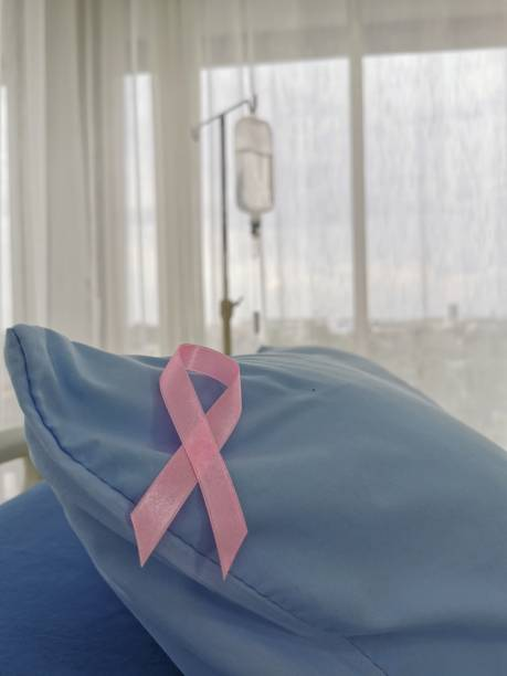 pink ribbon with hospital bad for patient in health care facility. breast cancer awareness concept. - breast cancer awareness стоковые фото и изображения