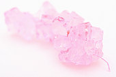 Cherry-flavored pink rock candy crystals on a string -- a classic American candy found on boardwalks and candy stores.