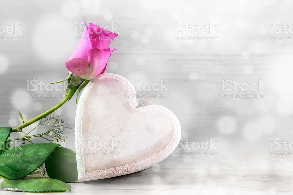 Pink rose and a wooden heart, bright bokeh background stock photo