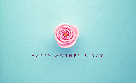 Pink rose and Happy Mother's Day message over turquoise background. Horizontal composition with copy space. Happy Mother's Day concept.